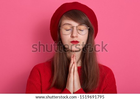 Image of beautiful woman wearing red clothing and beret, keeps palms pressed together in front of her, pouts lips, has regretful expression, keeping eyes closed, isolated over pink studio background.