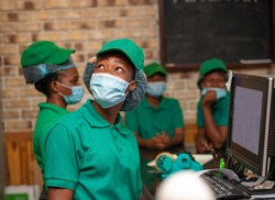 image of beautiful young African lady with face mask and cap-portrait of black girl with her colleagues blurred at background-protection at work place
