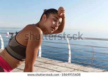 Image of beautiful young fitness woman panting and wiping sweat off forehead after jogging, finish run or workout, standing on a pier Photo stock ©