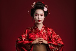 Image of beautiful young geisha woman in traditional japanese kimono isolated over red background
