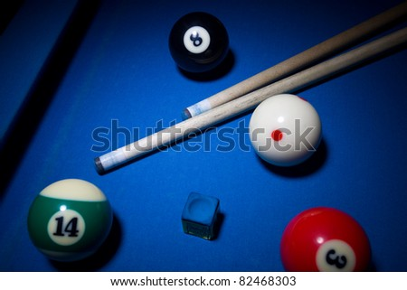 Image of billiard balls, cue and  chalk on blue table