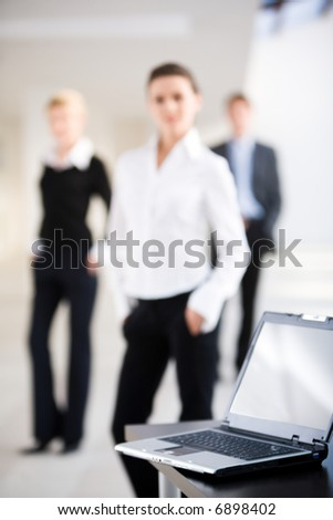 Image of black computer lying on the table on the background of three people