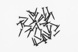 Image of black metal screws pile isolated on the white background. wood screws made of steel. Group of new strong black screws.