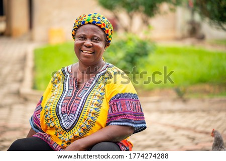 image of black mother with beautiful African print dress and head wrapper-African woman smiling in her garden-black woman sitting on a chair with joy and happiness.