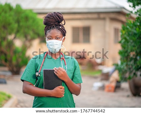 image of black nurse with face mask-young African health worker holding tablet with her stethoscope around the neck-portrait of beautiful African student nurse in her scrub dress during the covid-19