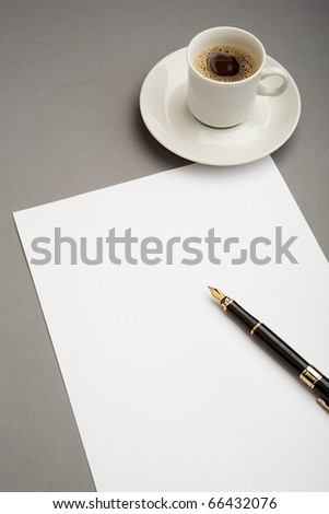 Image of blank paper sheet with penholder on workplace with cup of coffee near by