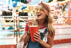 Image of blonde charming woman wearing girlish clothes drinking soda beverage from paper cup while walking in amusement park