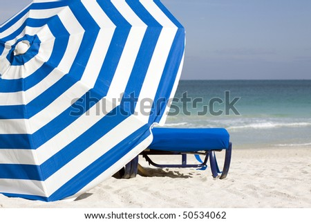 Image of blue lounge chair and blue and white striped umbrella set against the South Beach Atlantic shoreline in the late afternoon in Miami Beach.