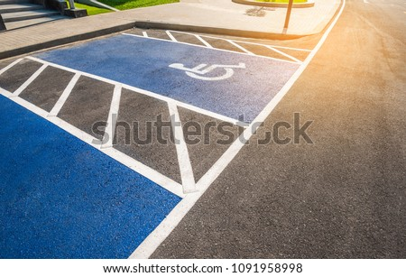 image of blue new handicapped symbol shows sign reserved for disability person on car parking space.