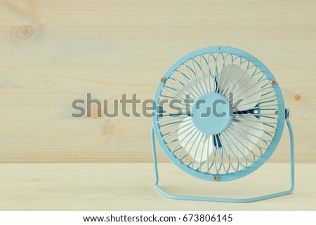 Image of blue retro fan on white wooden table. Vintage filtered. #673806145