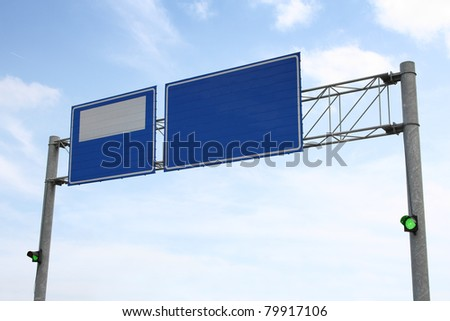 Image of blue road sign with green traffic lights on