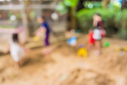image of blur kids at sand playground in public park for background usage .
