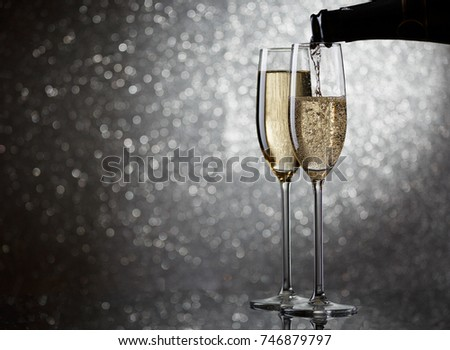 Image of bottle with champagne flowing in wine glasses on gray background #746879797