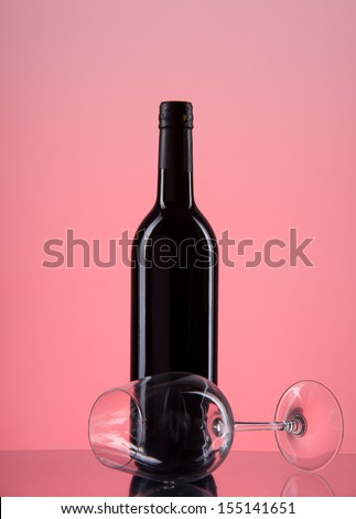 image of bottle with red wine and glass on a red gradient