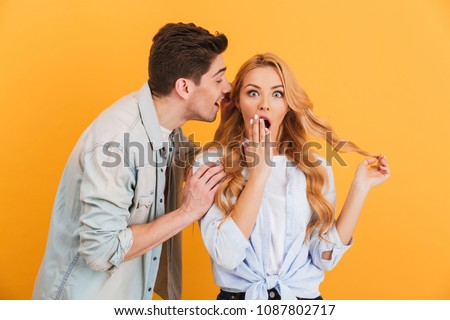Image of brunette man whispering secret or interesting gossip to surprised woman in her ear isolated over yellow background
