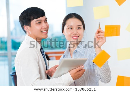 Image of business colleagues explaining business targets on the foreground