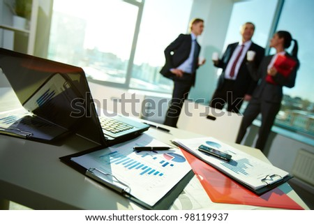 Image of business documents on workplace with three partners interacting on background