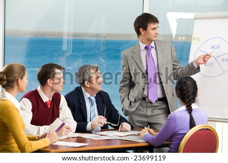Image of business group listening attentively to their young colleague making presentation on board