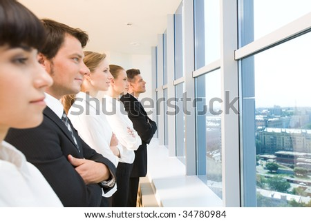 Image of business group standing in line and looking through window