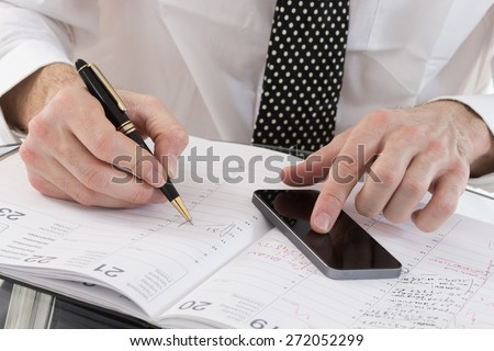 Image of  business man\' s hands planning on agenda book, and smart phone  in office