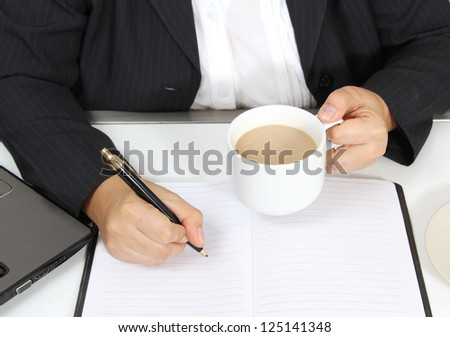 Image of business man write on book and hold hot coffee cup on left hand