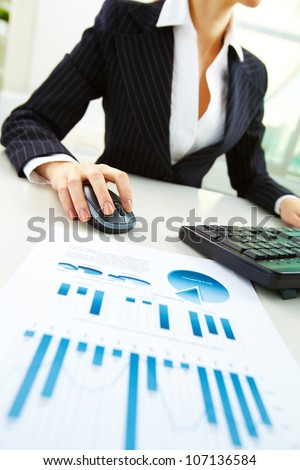 Image of business paper on background of female hands pushing keys of a computer mouse and keyboard