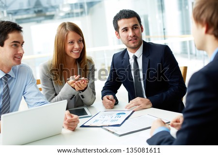 Image of business partners discussing documents and ideas at meeting - Shutterstock ID 135081611