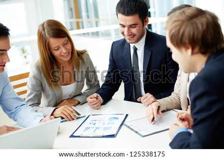 Image of business partners discussing documents at meeting - Shutterstock ID 125338175