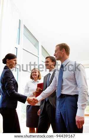 Image of business partners handshaking after signing new contract