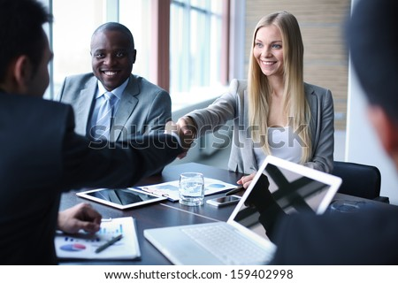 Image of business partners handshaking on background of their colleague