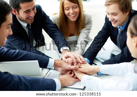 Image of business partners making pile of hands at meeting
