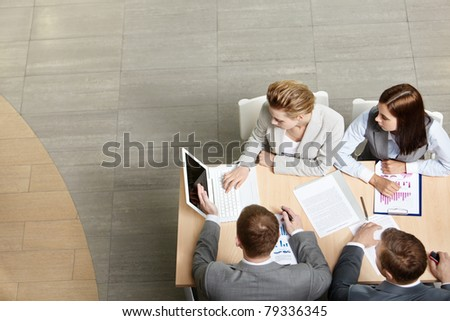 Image of business partners sitting at table and planning work - stock photo