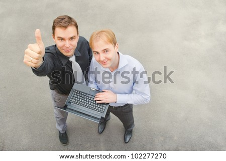 Image of business partners who raised their hands as a sign of success. Focus is made on top of the gray background of the empty street.