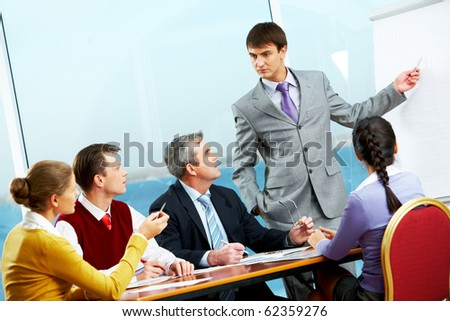 Image of business people listening to businessman showing at whiteboard