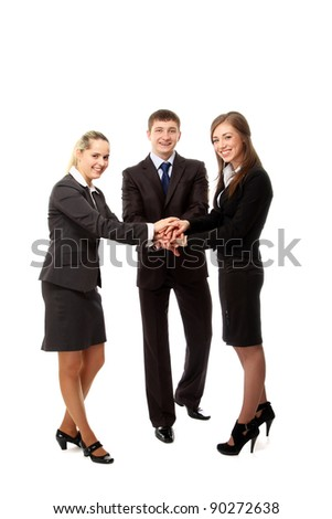 Image of business people putting their hands on top of pile and smiling. Isolated on white background
