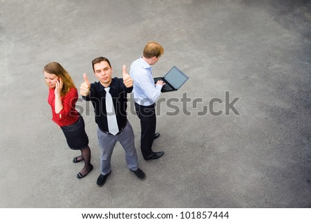 Image of business team of 3 people. Focus is made on top of the gray background of the empty street.