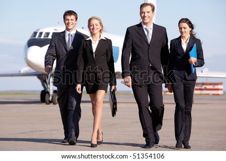 Image of business team walking through the airport