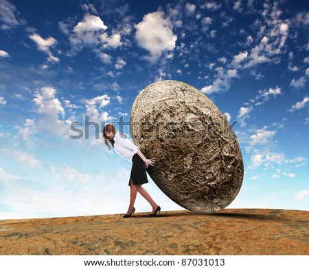 Image of business woman rolling a giant stone