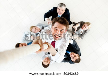 Image of businessman ascending up the rope with business people trying to stop him