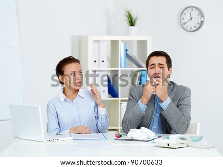 Image of businessman sneezing while his partner looking at him with anxiety in office