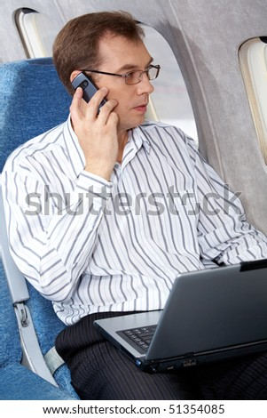 Image of businessman speaking on the phone in the plane