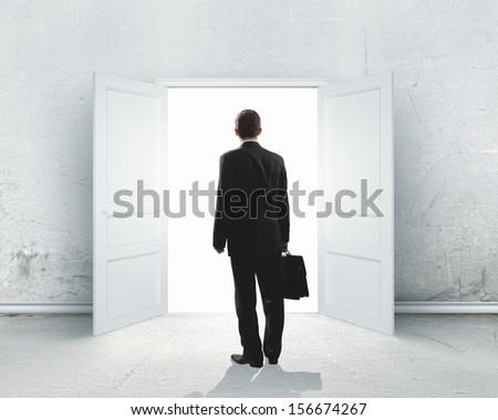 Image of businessman standing in front of opened door