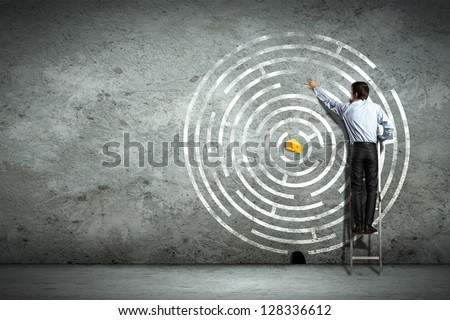 Image of businessman standing on ladder against maze picture