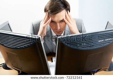 Image of businessman touching his head while looking at monitor with tired expression