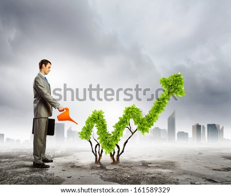 Image of businessman watering plant shaped like arrow