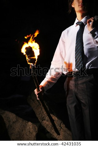 Image of businessman with flame in darkness