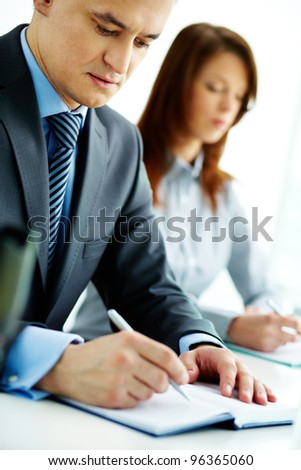 Image of businessman with pen writing in notebook at seminar