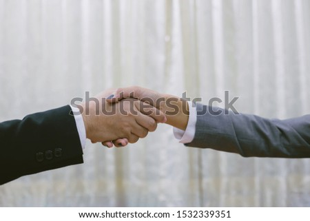 image of businessmen is shaking hands, businessman agrees to be the same cooperate in order to step through away the bad economy together.