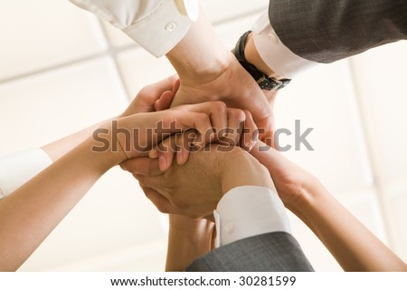 Image of businesspeople hands on top of each other as symbol of their