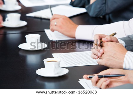 Image of businesspeople hands with pens, papers and cups of coffee near by